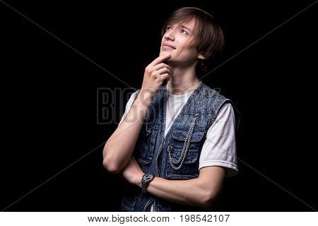 Young puzzled asian man looking up on black background