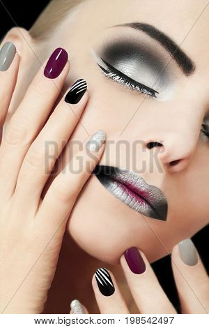 Black silver fashion glamorous manicure and makeup on a girl closeup on a black background.