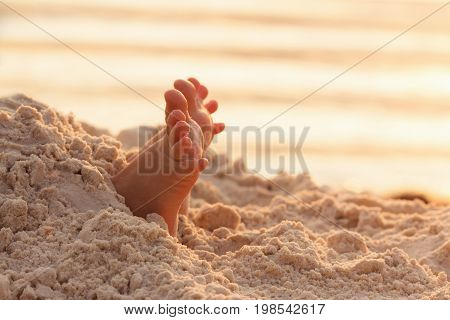 Closeup child kid feet on white sand beach. Sea on background concept of a relaxing holiday on the coast