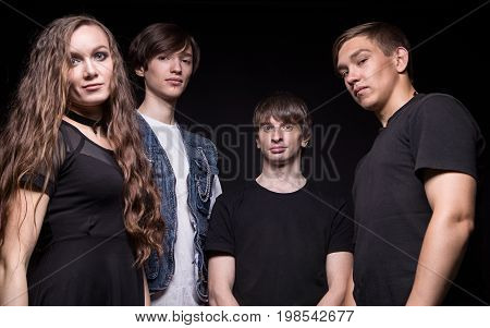 Photo of young rock musicians on black background