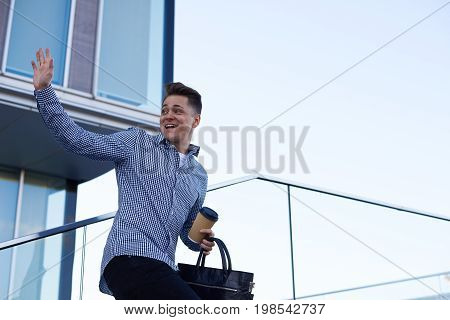 Attractive European male college student wearing shirt standing outside university building turning back and waving hand saying goodbye to his groupmates carrying leather bag and coffee-to-go