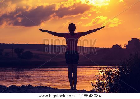 Silhouette of a young woman with arms raised on lake bank in the backdrop of the setting sun