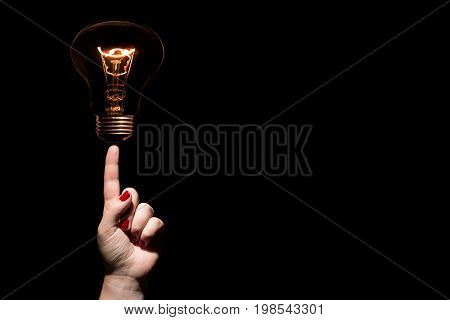Idea and success coincept. Glowing light bulb without wires on female hand with trigger finger and red nails on black background. Copy space
