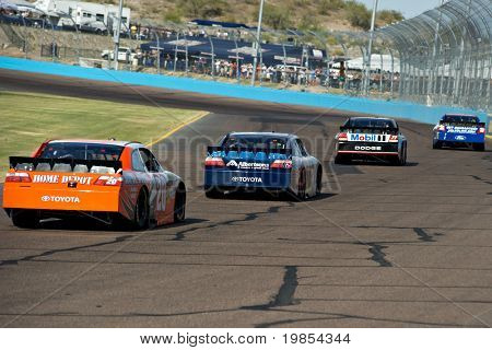 AVONDALE, AZ - APRIL 10: Joey Logano (#20) follows a group of cars into turn two at the Subway Fresh Fit 600 NASCAR Sprint Cup race on April 10, 2010 in Avondale, AZ.