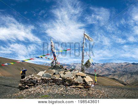 Buddhist chorten with mani stones and buddhists Lungta flags on Shey La Pass in Dolpo, Shey Phoksundo National Park, Nepal Himalayas