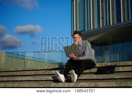 Thoughtful young European creative worker sitting on concrete stairs outdoors holding laptop computer in his hands working on project deep in thoughs. People creativity and modern technologies