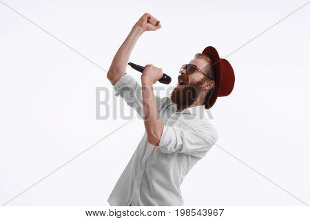 Emotional adult male entertainer actor or pop-singer wearing white shirt stylish hat and sunglasses holding wireless microphone speaking or singing in studio. Show entertainment and performance