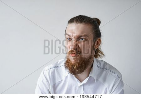 Picture of funny emotional young European office worker with facial hair grimacing screwing nose his look expressing dislike discontent or dissatisfaction. Negative human reaction and attitude