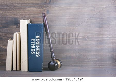 Business Ethics. Wooden gavel and books in background. Law and justice concept.