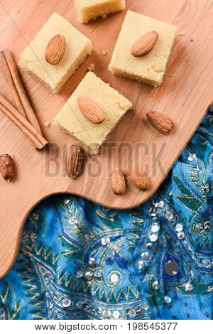 Indian traditional dessert halva made with flour and milk wih cinnamon and almonds served on embroidered blue cloth overhead view
