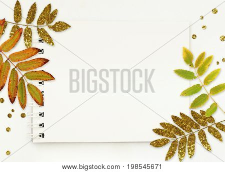 Notepad with white empty pages autumn leaves and glitter confetti on white background. Flat lay. Top view.