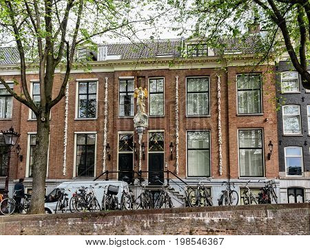 Amsterdam Netherlands - July 14 2017: Closely constructed houses with artistic heritage and gabled facades along the many water canals in Amsterdam.