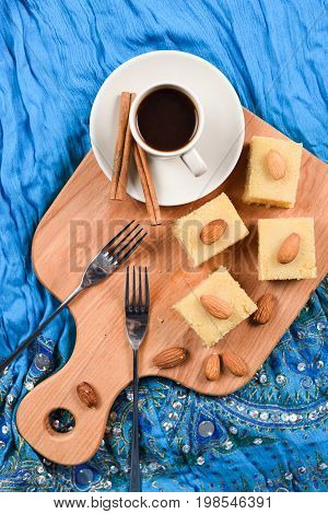 Semolina halva squares with almonds served with coffee on blue embroidered cloth flat lay. Indian sweets overhead view