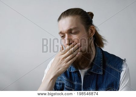 Studio shot of attractive fashionable guy with thick beard and hair knot dressed in denim vest over white t-shirt covering mouth while yawning feeling bored sleepy or tired. Body language