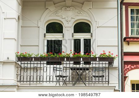 Nice balcony in classic building in Europe. balcony with flower pots and chairs