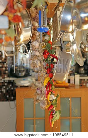 Wreath of garlic and chili peppers among the kitchen utensils above the kitchen island