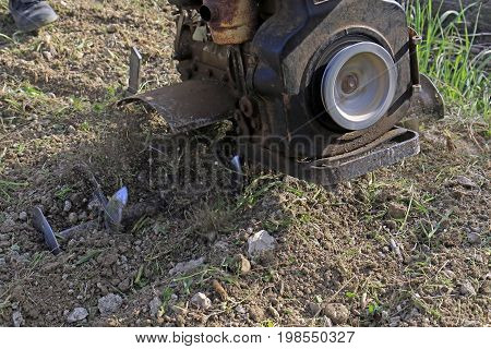 Motocultivator running and plowing the earth close up