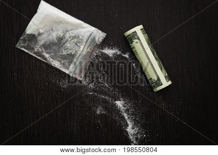 top view of a package with white powder and rolled-up bill