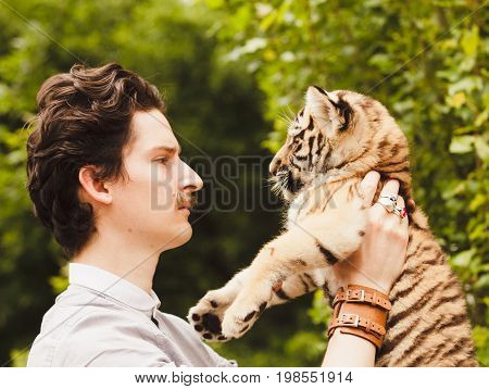 A man with a mustache looks into the face of a tiger cub otdoors