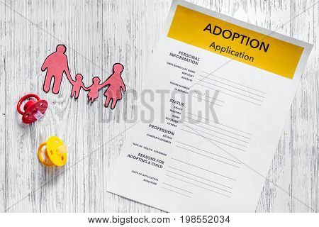 Adoption application on light wooden table background top view.