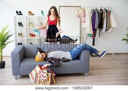 Bored man shopping with his girlfriend in a commercial street