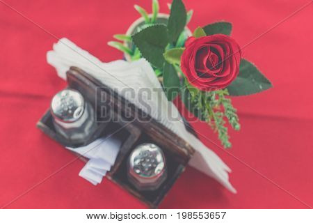 Closeup of beautiful fresh rose on a red table background. Restaurant. Bali island.