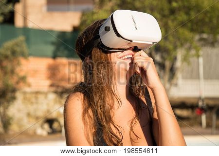 Smiling woman in swimwear using VR glasses sitting on poolside.