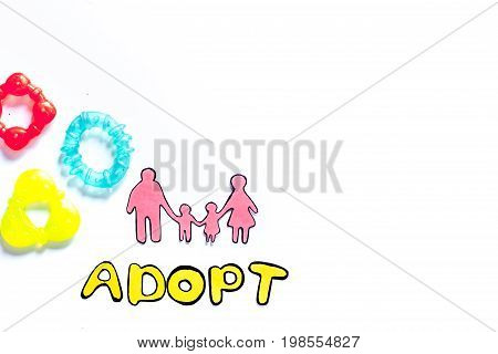 Adopt word, paper silhouette of family and toys on white background top view.