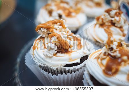 Homemade cupcakes with caramel syrup and fresh cream topping. Candy bar for birthday patry celebration, childhood, shallow focus. Sweet table - desserts, macaroni, cakes