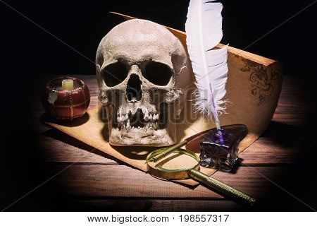 Literature concept. Old inkstand magnifying glass skull candle and quill on old vintage scroll and wooden background