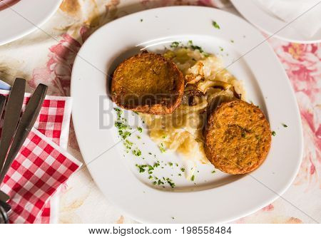 Fried potato pancakes on the plate indoors