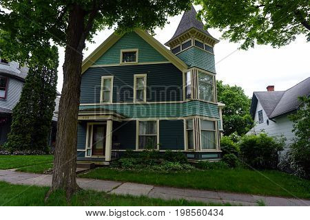 CADILLAC, MICHIGAN / UNITED STATES -  MAY 31, 2017: An historic green mansion with a turret in Cadillac's Courthouse Hill Historic District.