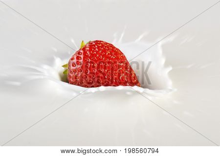 Fresh juicy strawberry falling into milk splashing.