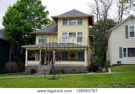 CADILLAC, MICHIGAN / UNITED STATES -  MAY 31, 2017: A yellow Victorian home with a wraparound front porch in Cadillac's Courthouse Hill Historic District.
