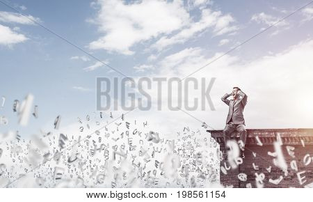 Frustrated businessman sitting on top and closing ears with hands