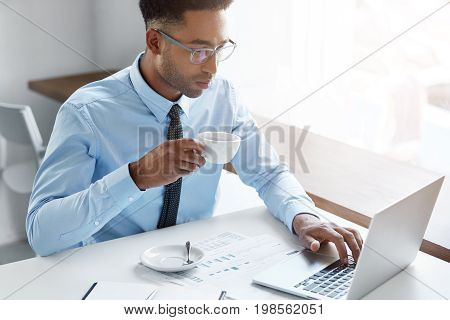 Professional Male Worker In Elegant Shirt With Tie, Sipping Fresh Coffee While Keyboarding At Laptop