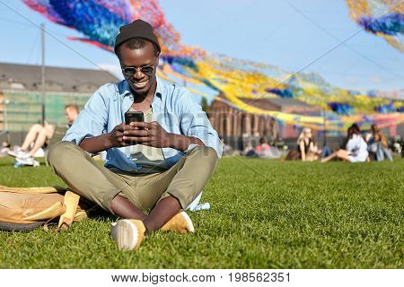 Smiling Black Male In Trendy Shades, Hat, Shirt And Trousers Sitting Crossed Legs At Green Lawn, Rea