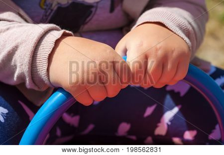 Summer. Sunny day. A child is sitting on a swing. Children playground. In the frame two hands hold onto the blue handrail. Horizontal frame. Ukraine. Kiev region