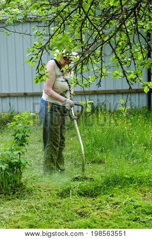 grandmother mows the grass on the plot