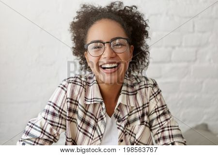 Happy Female With Dark Pure Skin And Crisped Hair Wearing Elegant Glasses And Shirt Smiling Sincerel