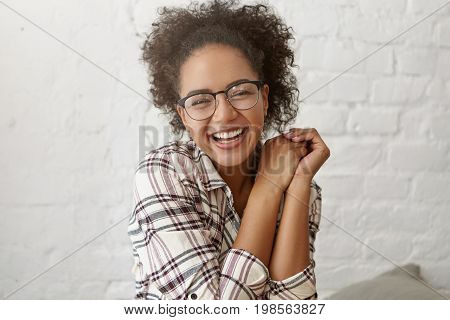 Pleased Mixed Race Woman With Curly Hair Wearing Big Eyewear And Checkered Shirt Closing Her Eyes Wi