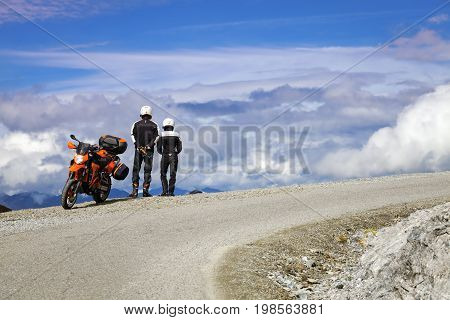 PASSO DELLO STELVIO (SO), ITALY - JULY 27, 2017: a couple of bikers look at the mountain panorama, along the bends of the world famous Passo dello Stelvio (between Lombardy and Trentino, Northern Italy Alps). Color image.