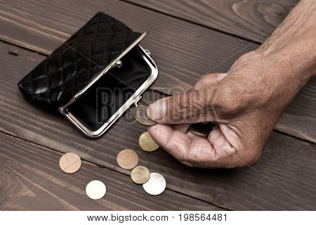 An Elderly Person Holds The Coins Over The Old Empty Wallet. The Concept Of Poverty In Retirement.