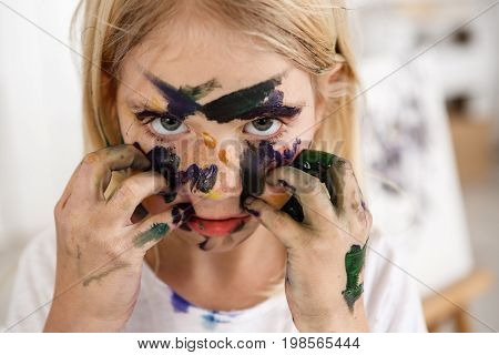 Close up portrait of beautiful little European girl with blond hair and freckles looking at the camera with her big eyes and touching her face with hands in paint, leaving colourful spots on face.