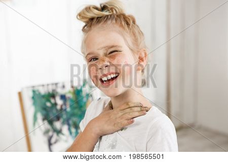 Small European blonde girl with painted face, laughing at camera and squinting in morning light. Creative mood and cheerful atmosphere mixed with shinny look of kid wearing white t-shirt.