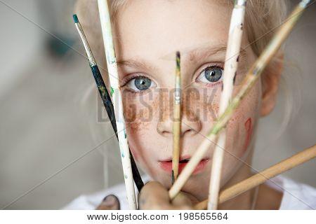 Little beautiful blonde girl with big blue eyes posing with brushes indoors. Tiny playing girl enjoying painting.