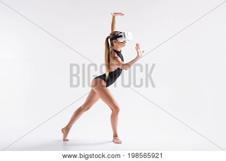 Solemn youthful girl in virtual reality headset is watching video and making lunge. She is leaning her body forward and touching fancy wall by hand