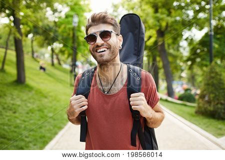 Positive bearded man with dark hair dressed in red t-shirt looking happy, wearing trendy sunglasses walking in the park and carrying guitar in case.