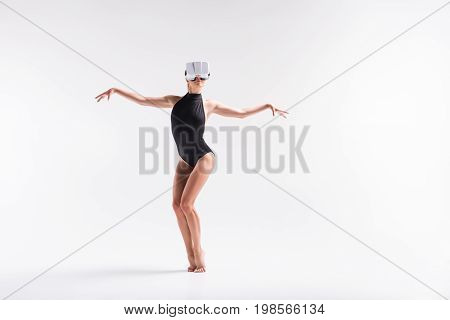 Full length portrait of serious young sporty girl in vr headset. She is standing on toes barefoot with half bent knees and arms to sides