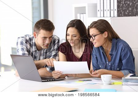 Three coworkers working at office comparing data with laptop and documents